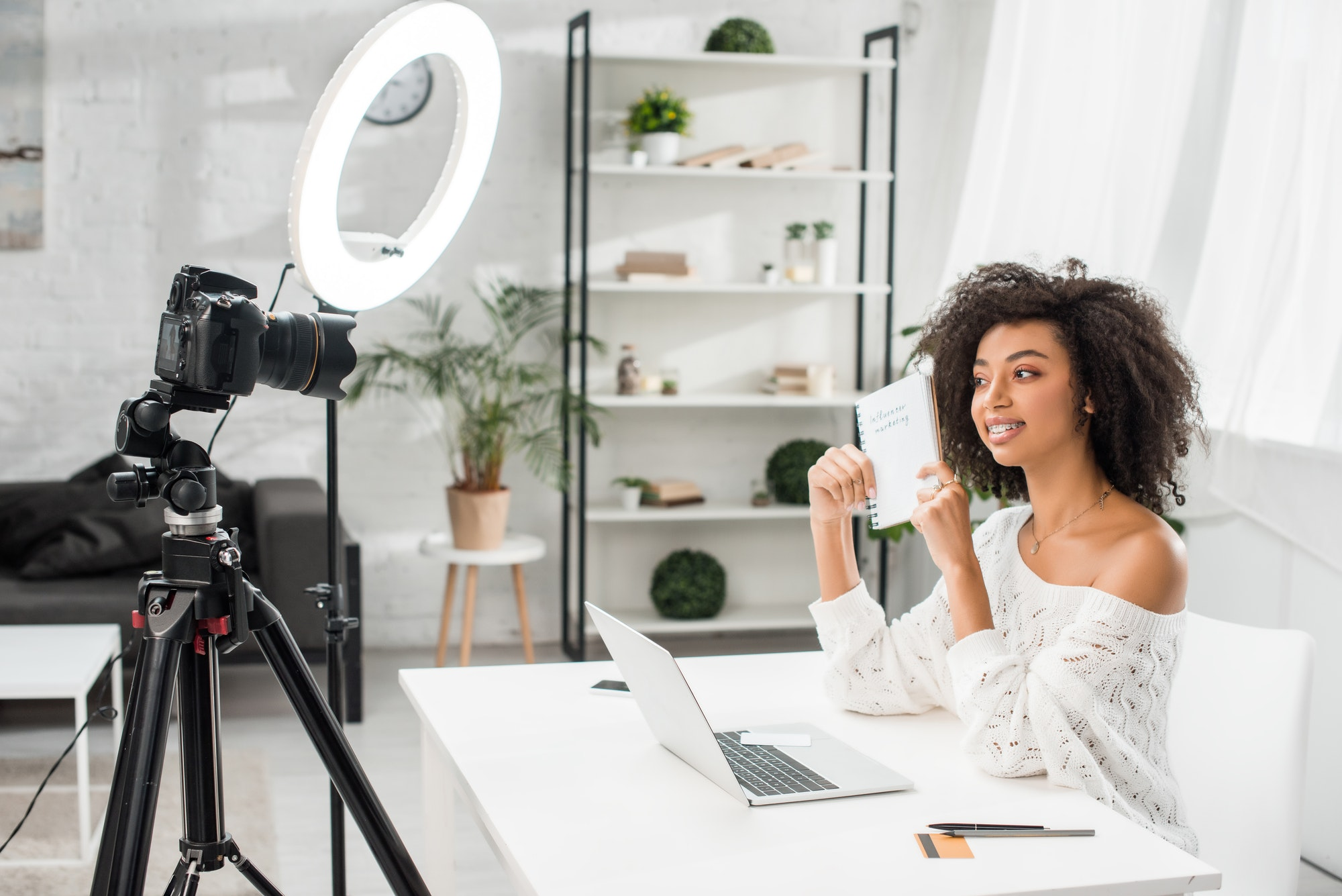 happy african american video blogger in braces holding notebook with influencer marketing lettering