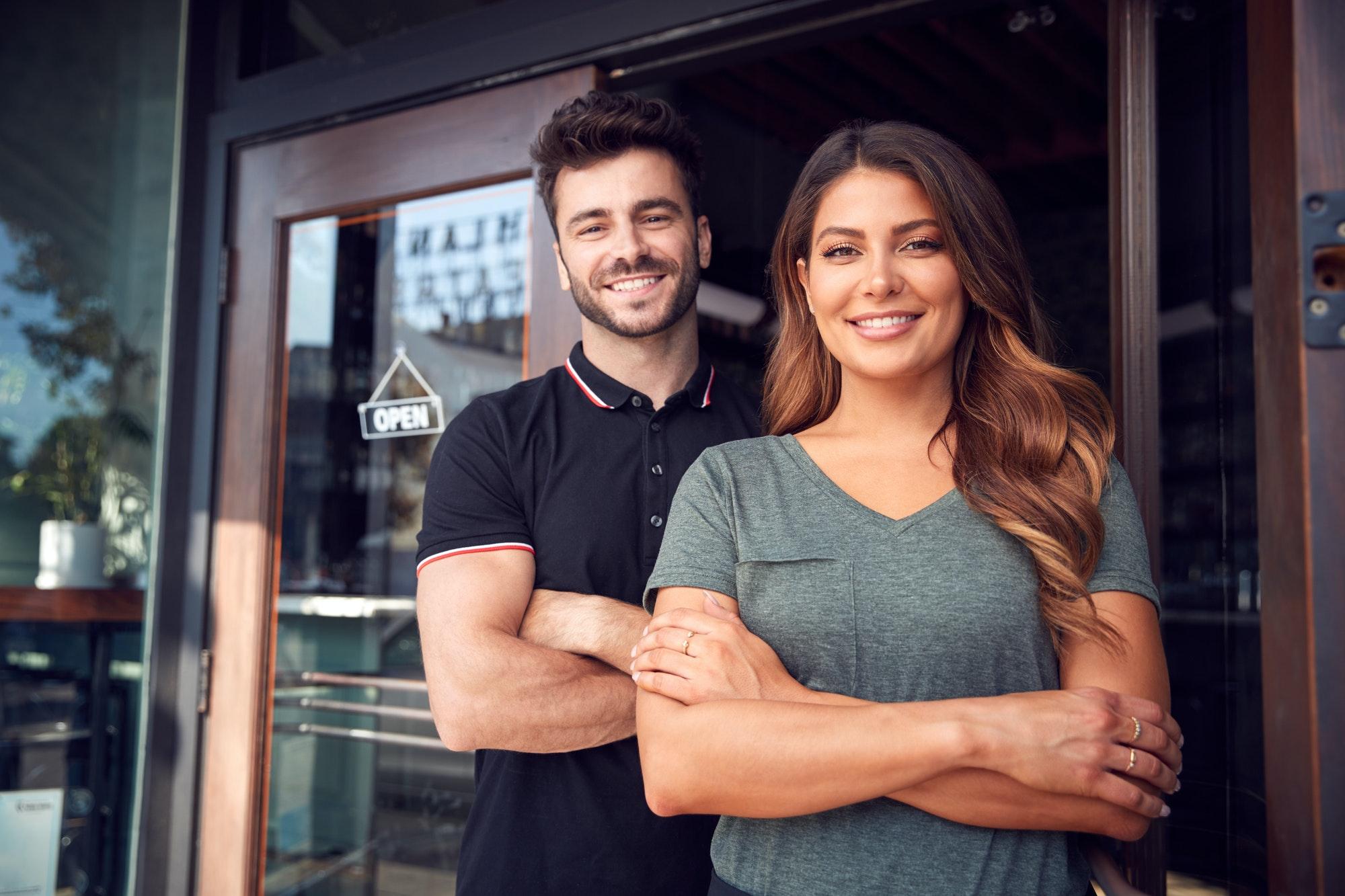 Portrait Of Couple Starting New Coffee Shop Or Restaurant Business Standing In Doorway